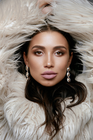 Fashion. Woman With Beauty Makeup In Fur With Jewelry. Portrait Of Young Sexy Model In Luxury Beige Faux Fur Jacket Wearing Long Gold Diamond Earrings. Women Winter Look. High Quality Image.