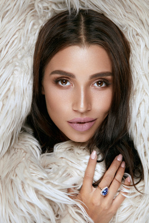 Beauty Makeup. Woman Face With Beautiful Facial Skin In Fur Closeup. Sexy Young Female Model With Luxury Make-up And Flawless Skin Wearing Glamorous Fur And Sapphire Diamond Ring. High Quality