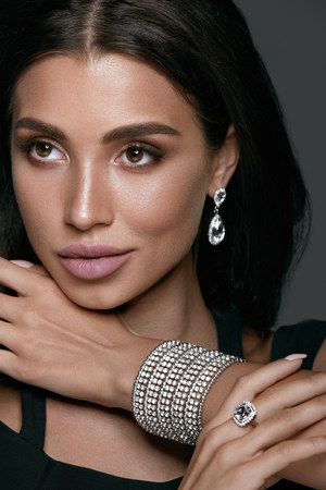 Jewelry Fashion. Beautiful Woman Wearing Diamonds. Portrait Of Gorgeous Female With Glamour Makeup On Beauty Face Wearing Black Evening Dress And White Gold Jewellery: Earrings, Bracelet And Ring