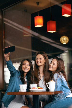 Friends Having Fun, Taking Photos In Cafe. Happy Gorgeous Young Women Taking Selfie Photos On Mobile Phone And Spending Leisure Time Together In Coffee Shop. Friendship. High Resolution.