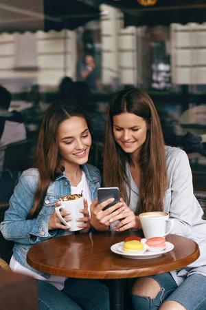 Happy Women Using Phone In Cafe. Beautiful Smiling Girls Friends With Cups Of Coffee Looking At Mobile Phone, Sitting At Table In Coffee Shop. High Resolution.