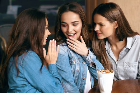 Meisjes roddelen. Vrienden die met koffie in koffie spreken. Glimlachende wijfjesvrienden die, koffie drinken drinken terwijl het zitten bij lijst in koffiewinkel. Vriendschap. Hoge resolutie.