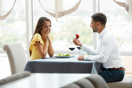 Proposal In Restaurant. Man Proposing Woman To Get Married With Engagement Ring. Handsome Young Male Making Romantic Proposal Of Marriage To Beautiful Female In Luxury Restaurant. High Quality Image. Stok Fotoğraf - 92440012