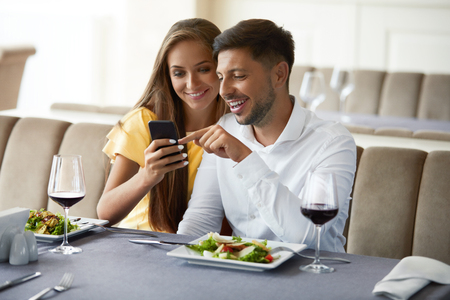 Couple In Love Looking On Phone Having Dinner In Restaurant. Lovely Young People Using Phone And Having Romantic Dinner In Restaurant. Relationships Concept. High Resolution. 版權商用圖片