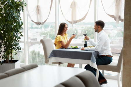 Lovely Couple Having Dinner In Luxury Restaurant. Young Handsome Man And Beautiful Woman Drinking Red Wine Eating Salad. Romantic Relationship. High Quality Image. Archivio Fotografico