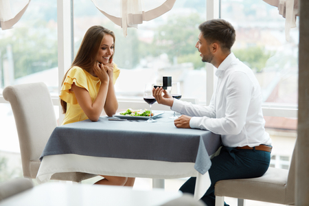 Proposal In Restaurant. Man Proposing Woman To Get Married With Engagement Ring. Handsome Young Male Making Romantic Proposal Of Marriage To Beautiful Female In Luxury Restaurant. High Quality Image. Banco de Imagens