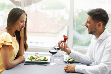 Proposal In Restaurant. Man Proposing Woman To Get Married With Engagement Ring. Handsome Young Male Making Romantic Proposal Of Marriage To Beautiful Female In Luxury Restaurant. High Quality Image. 写真素材