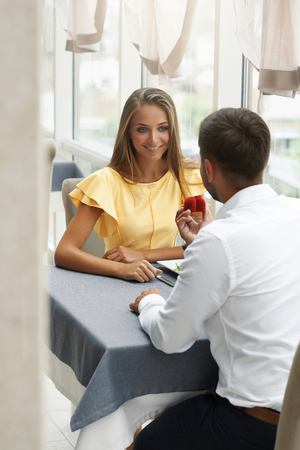レストランでの提案。婚約指輪で結婚する女性を提案する男。高級レストランで美しい女性に結婚のロマンチックなプロポーズをするハンサムな若 写真素材