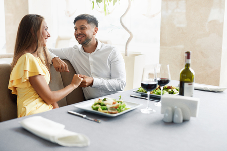 Romantische Paare, die für zwei im Restaurant zu Abend essen. Schöne glückliche Menschen in der Liebe sprechend, lachend und flirten beim Haben des romantischen Datums mit Wein und Lebensmittel im Luxusrestaurant. Hochwertiges Bild. Standard-Bild