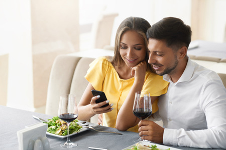 Couple In Love Looking On Phone Having Dinner In Restaurant. Lovely Young People Using Phone And Having Romantic Dinner In Restaurant. Relationships Concept. High Resolution.