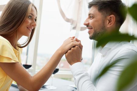 Schöne Paare in der Liebe im Restaurant. Hübscher Mann, der weibliche Hand am romantischen Datum küsst. Porträt des glücklichen jungen Mannes, der die Hand der Frau sitzt im Luxusrestaurant hält. Beziehung. Gute Qualität Standard-Bild - 92440073