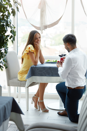 Proposal In Restaurant. Man Proposing Woman To Get Married With Engagement Ring. Handsome Young Male Making Romantic Proposal Of Marriage To Beautiful Female In Luxury Restaurant. High Quality Image. Stok Fotoğraf