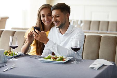 レストランで夕食を持って電話を見て愛のカップル。電話を使用して、レストランでロマンチックなディナーを持っている素敵な若者。リレーショ