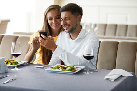 Couple In Love Looking On Phone Having Dinner In Restaurant. Lovely Young People Using Phone And Having Romantic Dinner In Restaurant. Relationships Concept. High Resolution. Stockfoto