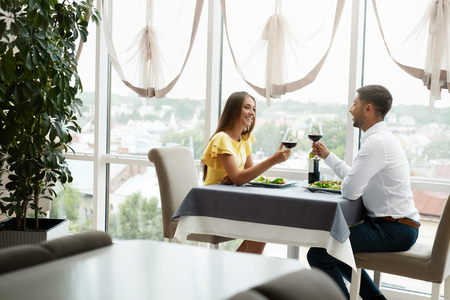 Beautiful Couple In Love On Romantic Date In Restaurant. Happy Smiling Couple Enjoying Romantic Dinner, Drinking Wine And Celebrating Holiday, Special Occasion. High Quality Image.