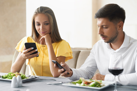 Pares usando telefones no jantar no restaurante. Homem novo e mulher que olham nos telefones celulares que sentem furados na data aborrecida no restaurante. Problemas de comunicação. Imagem de alta qualidade. Foto de archivo - 92440114