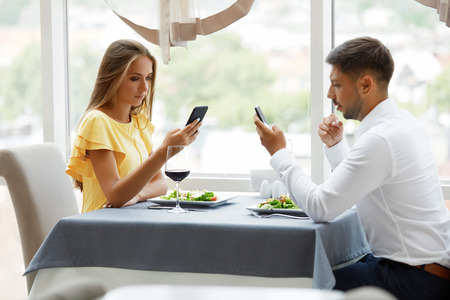 Communication Problem. Man And Woman With Phones On Date. Young Couple Using Cell Phone On Dinner In Luxury Restaurant, Having Relationship Problems. Dating Etiquette. High Resolution. Banque d'images
