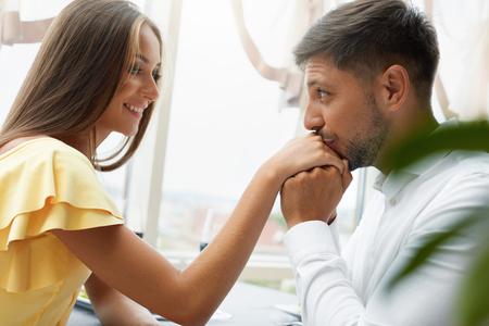 Schöne Paare in der Liebe im Restaurant. Hübscher Mann, der weibliche Hand am romantischen Datum küsst. Porträt des glücklichen jungen Mannes, der die Hand der Frau sitzt im Luxusrestaurant hält. Beziehung. Gute Qualität