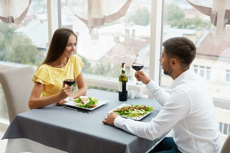 Hermosa pareja de enamorados en cita romántica en el restaurante. Feliz sonriente pareja bebiendo vino, comiendo ensalada y disfrutando de una cena romántica. Relación. Imagen de alta calidad.