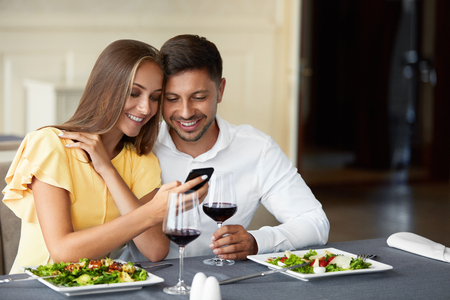 Couple In Love Looking On Phone Having Dinner In Restaurant. Lovely Young People Using Phone And Having Romantic Dinner In Restaurant. Relationships Concept. High Resolution. Stock Photo