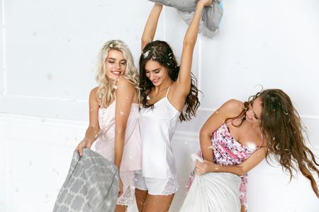 Kussengevecht. Sexy vrouwen met plezier thuis feestje. Mooie Glimlachende Vrouwelijke Modellen In Modieuze Sexy Pyjama's die en met Kussens bij Pyjama-Partij spelen vechten. Hoge resolutie