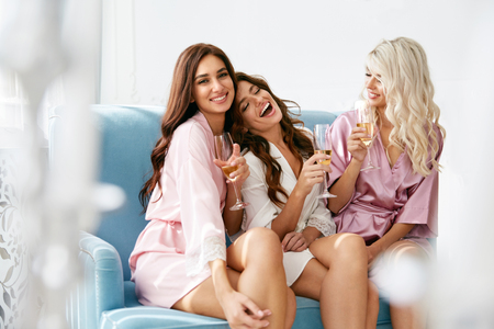 Girls Party. Beautiful Women Friends In Robes Having Fun At Bachelorette Party. Gorgeous Smiling Female Models In Silk Pink Pajamas Celebrating And Drinking Champagne At Hen Party. High Quality Image