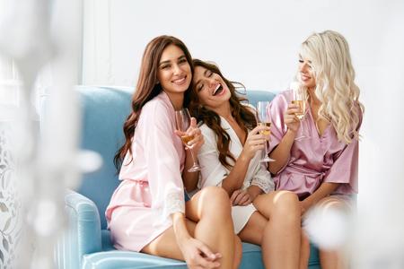 Meidenfeestje. Mooie vrouwen vrienden in gewaden plezier op vrijgezellenfeest. Schitterende glimlachende vrouwelijke modellen in zijde roze pyjama's vieren en drinken Champagne bij Hen Party. Afbeelding van hoge kwaliteit Stockfoto