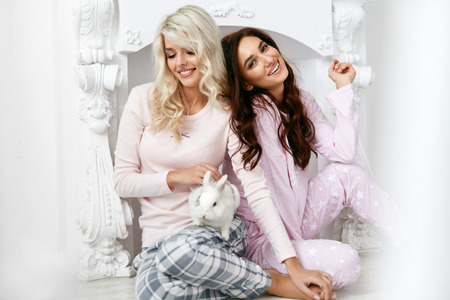 Women In Pajamas. Girls In Night Clothes Having Fun. Smiling Young Female Friends In Stylish Light Pink Sleepwear Sitting On Floor And Playing With White Rabbit At Home Party. High Resolution.
