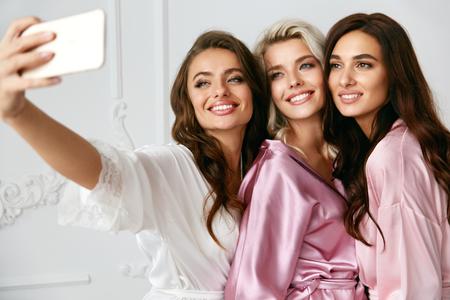 아름 다운 여자 가정 파티에서 전화에 사진을 만들기. 섹시 한 헤어 스타일와 메이크업 실크 핑크 로브 아름 다운 스마일 여자 친구 Selfies 복용 하 고