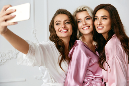 Beautiful Women Making Photos On Phone At Home Party. Beautiful Smiling Female Friends With Sexy Hairstyle And Makeup In Silk Pink Robes Taking Selfies And Having Fun At Pajama Party. High Quality