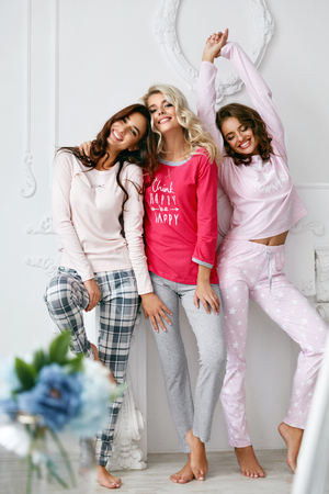 Girls In Pajamas. Beautiful Friends In Home Clothes. Gorgeous Smiling Young Female Models Having Fun And Enjoying Pajamas Party In Light Home Interior. Women Nightwear Clothing. High Quality Image Stock fotó