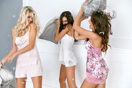 """Luta de Almofada. Mulheres """"sexy"""" que têm o partido do divertimento em casa. Modelos fêmeas de sorriso bonitos nos pijamas """"sexy"""" à moda que jogam e que lutam com os descansos no partido de pijama. Alta resolução"""