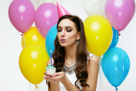 Portrait Of Beautiful Smiling Woman In Festive Dress And Birthday Hat Holding Cupcake With Candle In Hands, Celebrating Holiday. High Resolution. Stockfoto