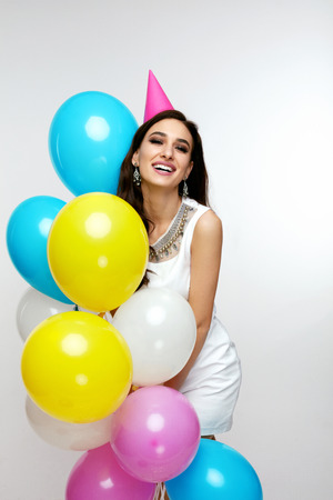 Portrait Of Smiling Young Female In Stylish White Dress With Balloons Having Fun And Celebrating Her Birthday Party. Holiday. High Quality
