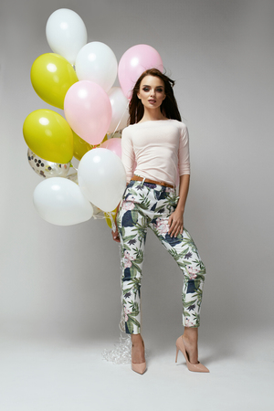 Full Length Portrait Of Gorgeous Sexy Woman In Fashion Clothes With Bright Colorful Balloons On Grey Background. Girl Clothing Style. High Quality Image. Foto de archivo