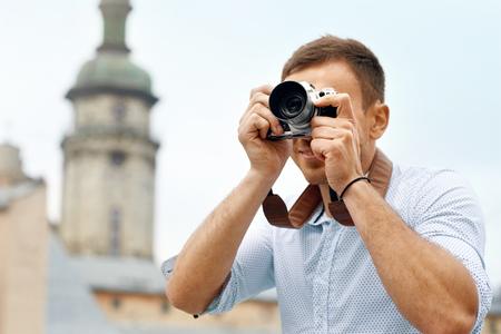 사진 거리에 사진을 찍는 관광 남자. 오래 된 도시에서 산책하는 동안 재미있는 사진의 카메라를 들고 잘 생긴 웃는 남자의 초상화. 여행 개념입니다.