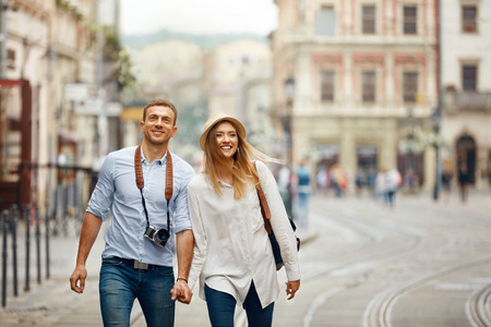 Travel. Tourist Couple Traveling, Walking On Street. Portrait Of Beautiful Young Woman And Handsome Man In Stylish Clothes Sightseeing City Attractions, Looking At Architecture. High Resolution. 스톡 콘텐츠