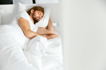 Man Sleeping On Bed In Morning. Portrait Of Handsome Young Male With Beard Resting On White Linen In Light Bedroom. Healthy Sleep. High Quality Image.
