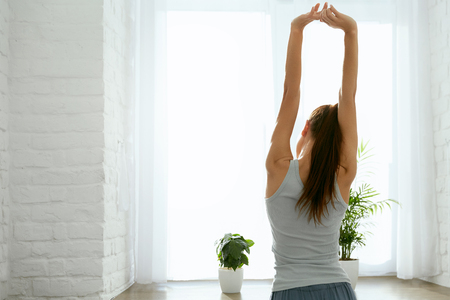 Woman Stretching Hand Near Window In Morning. Portrait Of Beautiful Female In Home Clothes Standing Near Window And Stretching Body After Waking Up. High Resolution.