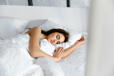 Sleep. Young Woman Sleeping In Bed. Portrait Of Beautiful Female Resting On Comfortable Bed With Pillows In White Bedding In Light Bedroom In Morning. People Sleep. High Quality Image.