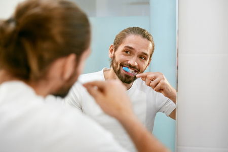 Man Brushing Teeth. Male Cleaning Teeth In Bathroom. Portrait Of Young Handsome Male Holding Toothbrush In Hand, Looking In Mirror In Bathroom. Dental Hygiene. High Resolution.