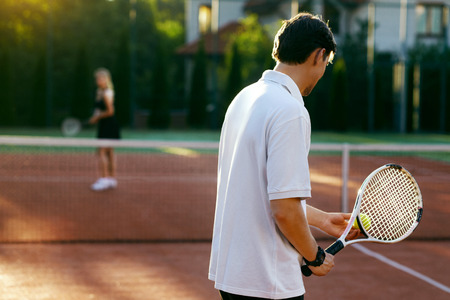 Young People Playing Tennis Outdoors. Healthy Active Man And Woman Holding Rackets In Hands Playing Tennis Match On Open Court On Sunny Summer Day. Sports And Lifestyle. High Resolution.