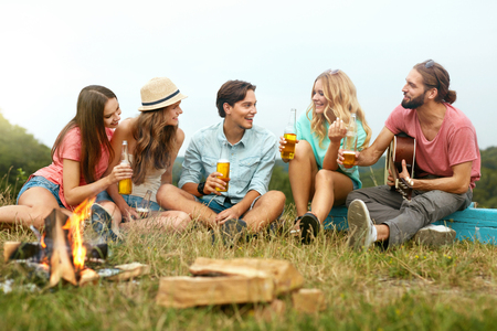 Happy Friends Having Fun In Nature On Vacations. Young Smiling People Sitting Near Bonfire Holding Drinks And Enyoing Picnic Party Outdoors On Summer Weekend. Friendships Concept. High Quality Image.