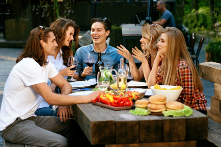 Happy Friends In Outdoor Picnic Party Having Fun. Smiling Young People Eating Healthy Food And Drinking Wine At Table In Nature. Beautiful Women And Men Laughing And Communicating. High Quality Image