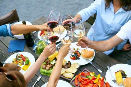 People Cheering With Drinks At Outdoor Dinner Party. Close Up Of Friends Hands Raising Toast With Glasses Of Wine, Enjoying Outdoor Picnic While Sitting At Table With Food. Cheers. High Quality Image. Foto de archivo