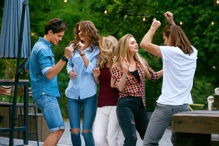 Happy vrienden dansen, plezier maken en genieten van een feestje buitenshuis. Mooie lachende jonge mensen in stijlvolle casual kleding lachen, vieren en dansen in het park op zomerweekend. Hoge resolutie. Stockfoto