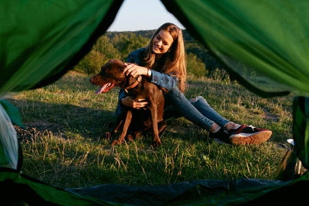 Beautiful Smiling Girl Playing With Pet, Sitting Near Tent On Grass And Enjoying Summer. Travel Concept. High Quality Image.