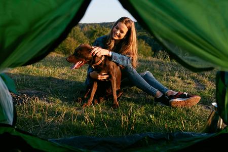 Menina de sorriso bonita que joga com o animal de estimação, sentando-se perto da barraca na grama e apreciando o verão. Conceito de viagem. Imagem de alta qualidade. Foto de archivo - 94714942