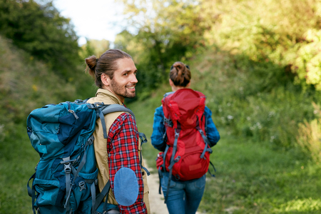Portrait Of Beautiful Smiling Young People With Backpacks Hiking In Mountains On Weekend In Summer. Couple Travel In Nature Concept. High Resolution. Stock Photo