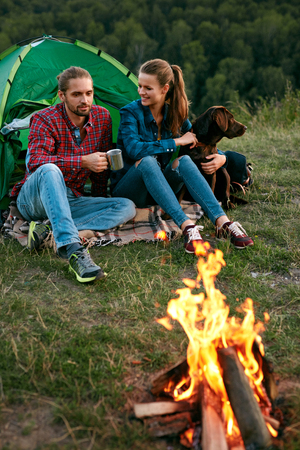Smiling Young People Sitting Near Camping Tent And Playing With Pet, Traveling On Weekend. High Quality Image Stock Photo